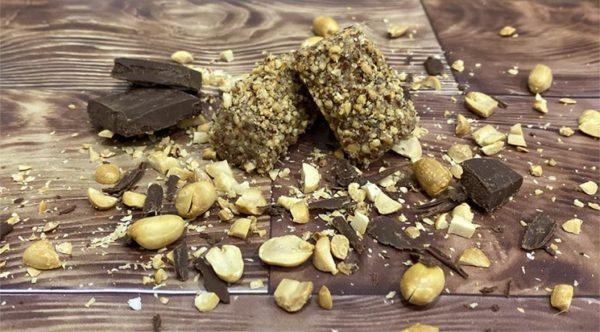 posni kolači valjkastog oblika sa kikirikijem na drvenoj podlozi oko njih posuta čokolada i kikiriki